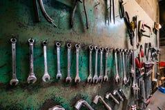 Wand mit verschiedenen Metallinstrumenten in wenig Fabrikraum Stockfoto