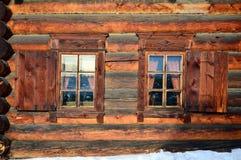 Wand mit zwei Windows von Holzhäusern von den runden Klotz Winter Das Museum der hölzernen Architektur unter dem Offenen Himmel R Lizenzfreies Stockfoto