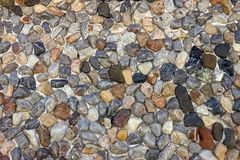 Wand von kleinen mehrfarbigen Kieseln Die Steinoberfläche des wa Stockbilder