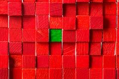 Wand von roten Bauklötzen, grüner Block in der Mitte Stockbild