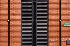 Wandbeschaffenheit des roten Backsteins und metallische Türen mit Notausgang unterzeichnen stockbild