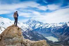 Wandelaar bij de bovenkant van een rots met rugzak stock fotografie