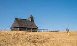 Wandelaar dichtbij raditional houten kerk op Velika Planina Stock Afbeelding