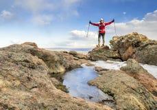 Wandelaar die bereikend bergbovenkant genieten van royalty-vrije stock afbeeldingen