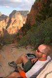 Wandelaar die in bergen rust Stock Fotografie
