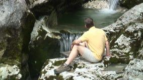 Wandelaar die bij een waterval rusten stock video