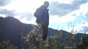 Wandelaar die met rugzak bovenop een berg met zon de wandelen flakkert in langzame motie Jonge mensen gezonde actieve levensstijl stock footage