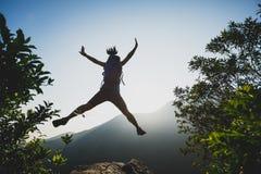 Wandelaar die op de bergbovenkant van de de zomerzonsopgang springen Stock Afbeelding