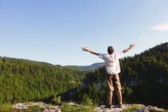 Wandelaar die van adembenemend landschap vanaf bovenkant van klip in Zwitserland genieten stock afbeeldingen