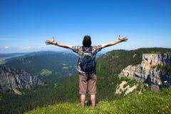 Wandelaar die van adembenemend landschap vanaf bovenkant van klip in Zwitserland genieten stock foto's