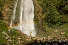 Wandelaar die van de Toneelwaterval met regenboog genieten stock foto's