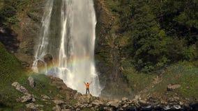 Wandelaar die van de Toneelwaterval met regenboog genieten Langzame Motielengte stock videobeelden