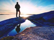 Wandelaar in donkere sportkleding met polen en sportieve rugzak Kustlijnsleep op rotsachtige kust De alleen toerist geniet van Royalty-vrije Stock Foto
