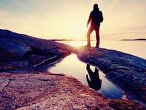 Wandelaar in donkere sportkleding met polen en sportieve rugzak Kustlijnsleep op rotsachtige kust De alleen toerist geniet van Royalty-vrije Stock Afbeelding