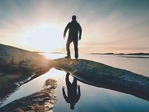 Wandelaar in donkere sportkleding met polen en sportieve rugzak Kustlijnsleep op rotsachtige kust De alleen toerist geniet van Stock Fotografie