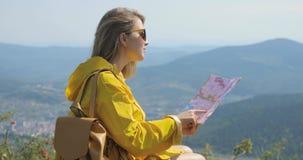Wandelaar in een gele regenjas die kaart vanaf bergbovenkant bekijken vrouw met kaart in bergen 4k stock video