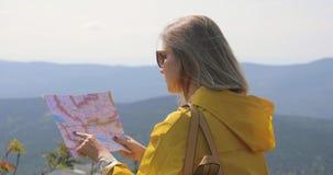 Wandelaar in een gele regenjas die kaart vanaf bergbovenkant bekijken vrouw met kaart in bergen 4k stock footage