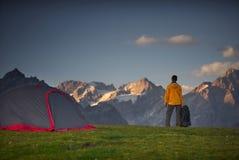 Wandelaar in een kamp en het bekijken bergen in een sumerdag royalty-vrije stock afbeeldingen