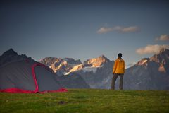 Wandelaar in een kamp en het bekijken bergen in een sumerdag stock foto