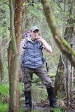 Wandelaar in het moerassige bos die onderbreking voor drank nemen Stock Foto's