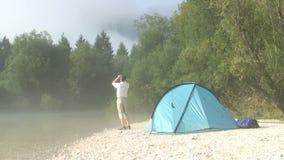 Wandelaar met binoculair naast zijn tent stock videobeelden