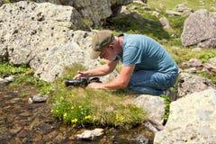 Wandelaar met camera die beeld van kleine stroom nemen Stock Fotografie