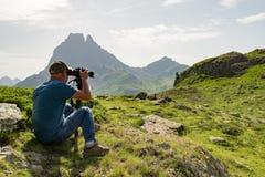 Wandelaar met camera die beeld van mooie berg nemen royalty-vrije stock afbeelding