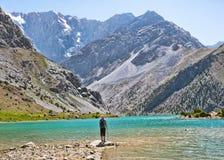 Wandelaar met rugzak dichtbij Kulikalon-meer op rotsachtige berg stock fotografie