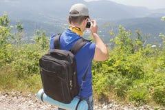 Wandelaar met rugzak die zich bovenop de berg bevinden en een beeld van vallei nemen Stock Foto's