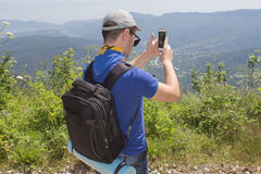 Wandelaar met rugzak die zich bovenop de berg bevinden en een beeld van vallei nemen Stock Afbeelding