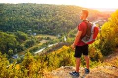 Wandelaar met rugzak die zich bovenop een berg bevinden Stock Foto's