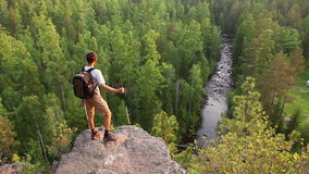Wandelaar met rugzak die zich op een berg bevinden stock videobeelden