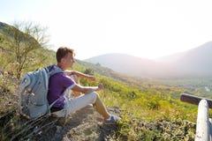 Wandelaar met rugzak het ontspannen op een weg van berg Royalty-vrije Stock Afbeeldingen