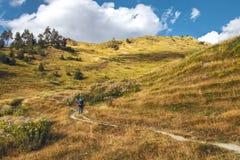 Wandelaar met rugzak het uitgaan in de bergen stock afbeeldingen