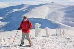 Wandelaar op de bovenkant van onderstel achter piek Stock Foto's