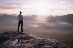 Wandelaar in sportieve kostuumtribune op piek in rots en horloge over mist stock foto's