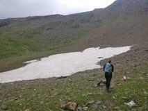 Wandelaarmeisje die op een steen en sneeuwgebied in de bergen met rugzak lopen royalty-vrije stock afbeelding