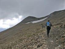 Wandelaarmeisje die op een steen en sneeuwgebied in de bergen met rugzak lopen stock foto's