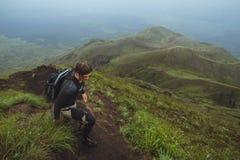 Wandelaarmens die een steile muur in berg beklimmen Royalty-vrije Stock Afbeeldingen