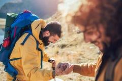 Wandelaarmens die hulp op stijging gelukkige het overwinnen hindernis krijgen stock afbeeldingen