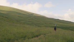Wandelaarmens die op groen gebied op bergen en heuvelsachtergrond lopen stock video