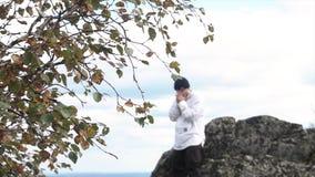Wandelaarmens die zich dichtbij de kei, wat betreft zijn gezicht achter een boomtak bevindt lengte Gele en groene bladeren van ee stock foto