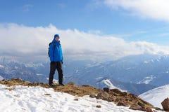 Wandelaarmens met rugzak die zich bovenop een berg op bac bevinden Royalty-vrije Stock Afbeeldingen