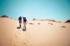 Wandelaars die zandduinen beklimmen Royalty-vrije Stock Foto's