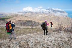Wandelaars op een steenachtige overzeese kust Royalty-vrije Stock Foto's