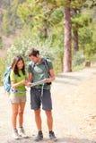 Wandelaars - wandelend paar dat kaart bekijkt Stock Foto