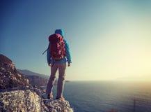 wandelaartribune op de rand van de de bergklip van de zonsopgangkust Stock Foto's
