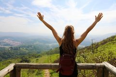 Wandelaarvrouw die zich met handen bevinden die omhoog de bovenkant bereiken Het meisje stemt in met een zon De succesvolle open  royalty-vrije stock foto