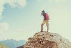 Wandelaarvrouw die zich op rots bevinden stock afbeeldingen
