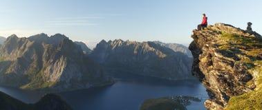 Wandelaarzitting boven de rotsachtige Eilanden van landschapslofoten, Noorwegen royalty-vrije stock afbeeldingen